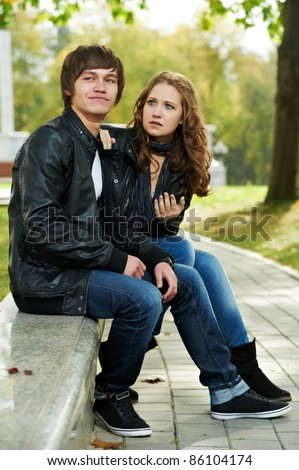 conflict and stress in young people couple relationship outdoors. Grining man and sad girl - stock photo