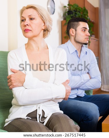 Conflict between aged woman and her young handsome boyfriend at home  - stock photo