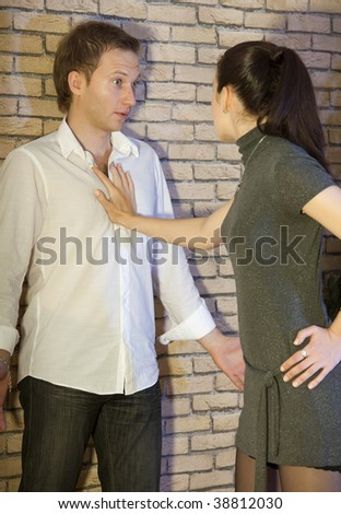 conflict between couple, woman pinned man to the wall - stock photo