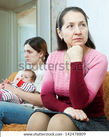 Conflict between the mature mother and her daughter with baby at home - stock photo