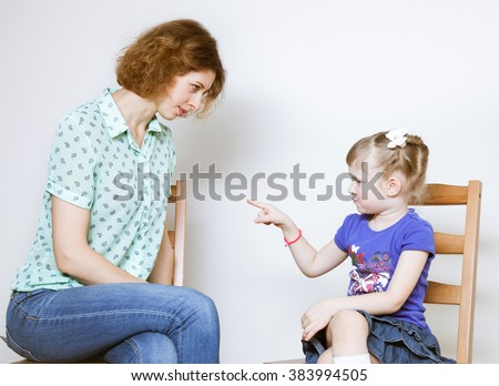 Conflict between young mother and her little daughter, neutral background - stock photo