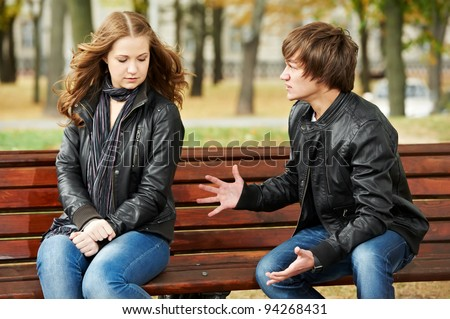 conflict in young people relationship. Anger man and sad girl outdoors - stock photo