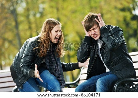 conflict in young people relationship. Furious anger girl and man stopped ears with hands - stock photo