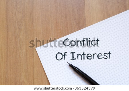 Conflict of interest text concept write on notebook with pen - stock photo