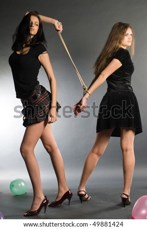 Conflict of two women. The senior dominates over younger with the connected hands - stock photo