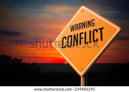 Conflict on Warning Road Sign on Sunset Sky Background. - stock photo