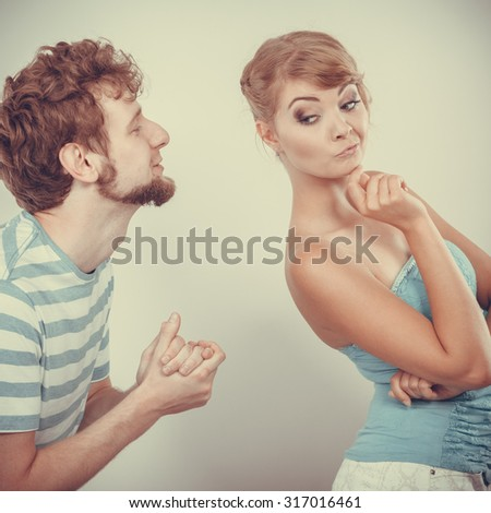 Conflicted couple. Relationship problem. Boyfriend trying to convince girlfriend. Man asking for forgivness. Husband apologizing wife. Unhappy, upset, angry woman refuses apology. - stock photo