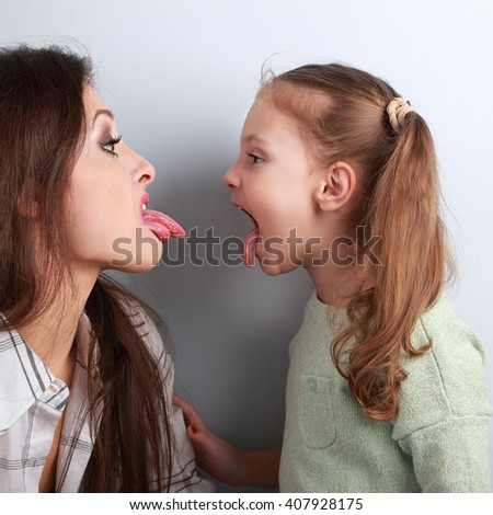 Conflicting funny mother and daughter disputing and showing each other the tongues. Closeup portrait - stock photo