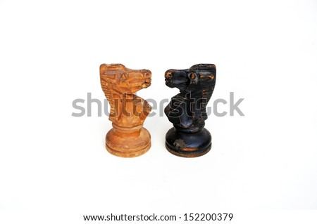 Confrontation of antique chess knights isolated on a white background - stock photo
