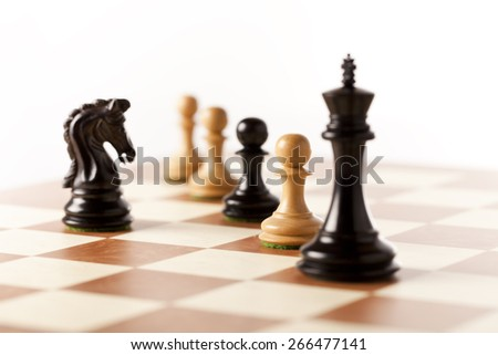 Confrontation - white and black chess knights standing next to each other on a chessboard - stock photo