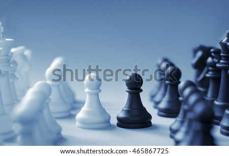 Confronting black and white chess pieces on a light blue background with slight set shadow