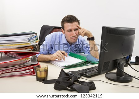 Confused accountant looking at some info on the display of his computer, surrounded by huge piles of documents.