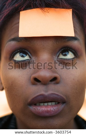 Confused African American businesswoman with post it reminder note on forehead - focus on eyes - stock photo