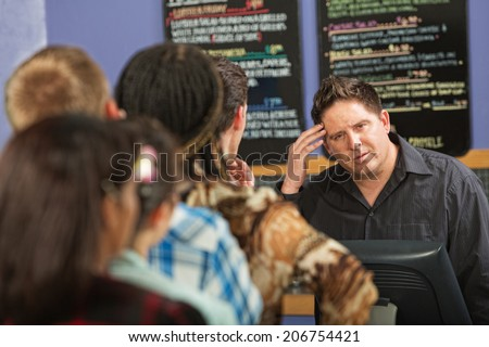 Confused barista at cash register in cafe - stock photo