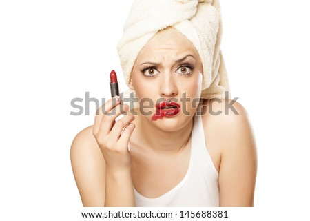 confused blonde girl with a towel on her head holding a lipstick in hand - stock photo
