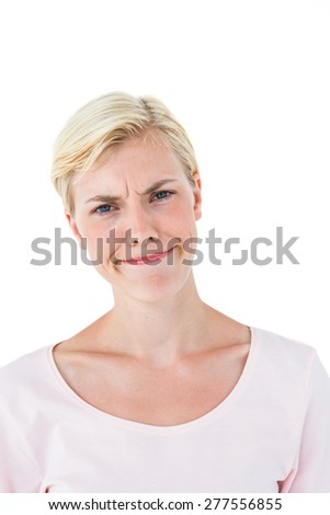 Confused blonde woman looking at camera on white background - stock photo