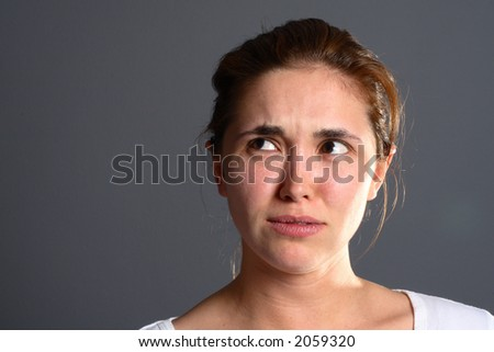 Confused brunette girl in front of grey background