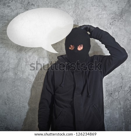 Confused burglar with speech balloon, thief with balaclava caught confused and without idea in front of the grunge concrete wall. - stock photo
