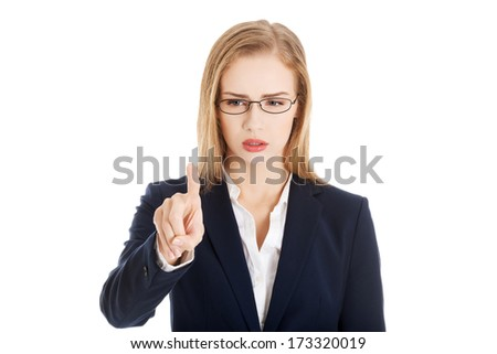Confused business woman in eyeglasses is looking at her finger. Isolated on white. - stock photo