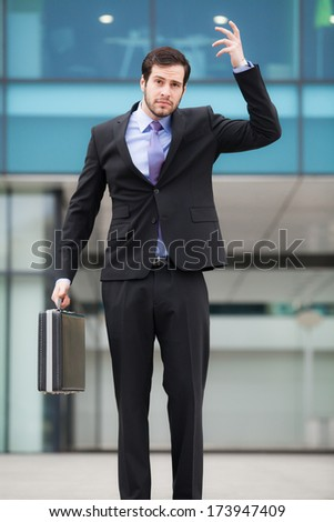 confused businessman in front of an office building with a briefcase - stock photo