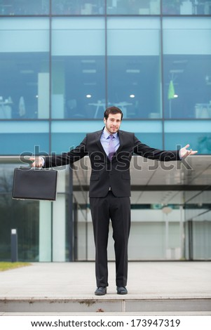 confused businessman in front of an office building with hands open  - stock photo