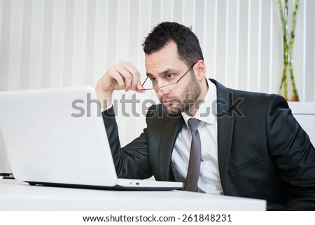 Confused businessman looking at laptop at office. Resolving some problem. - stock photo