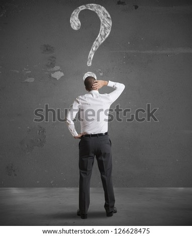 Confused businessman looking at question mark in the wall - stock photo