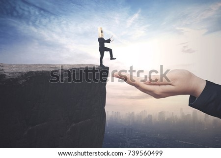 Confused businessman with cardboard head walking on the cliff toward a helping hand