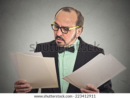 Confused businessman with glasses looking at documents holding too many contracts papers isolated on grey office wall background. Human face expression, emotion - stock photo