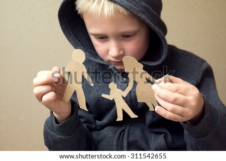 Confused child with broken paper family, family problems, divorce, custody battle, suffer concept  - stock photo