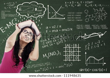 Confused college student with formulas on the blackboard and covering her head by textbook. shot at class - stock photo
