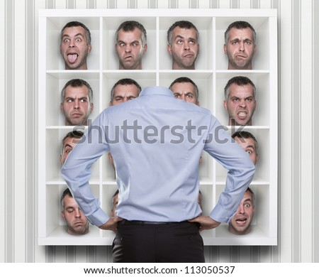 Confused conceptual image, young businessman choosing which face expression to wear