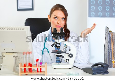 Confused doctor woman working with microscope in laboratory - stock photo