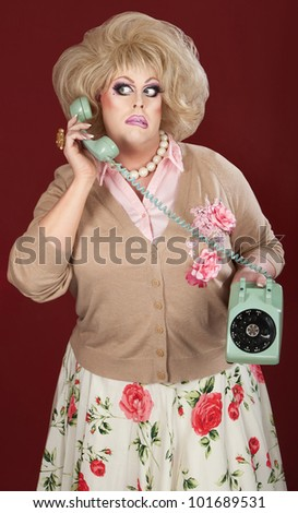 Confused drag queen on phone call over maroon background - stock photo