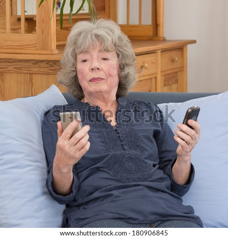 Confused elderly lady with two mobile phones on her sofa, square - stock photo