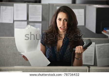 Confused female employee holds documents and a telephone - stock photo