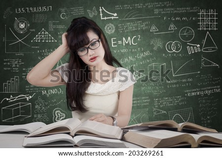 Confused female student reading many books for exam in the class