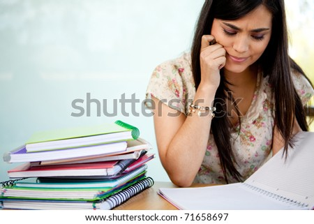 Confused female student with a pile of notebooks - stock photo