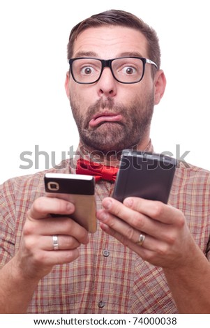 Confused geeky man with two gadgets, making a face.  Isolated on white. - stock photo