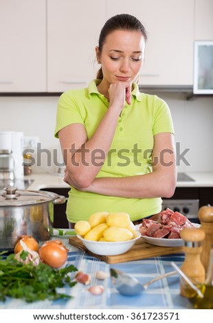Confused housewife thinking what to prepare for dinner