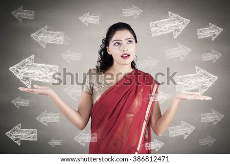Confused Indian businesswoman in traditional dress looking at arrows on grey background - stock photo