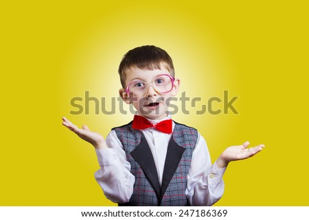 Confused little boy nerd with glasses isolated on yellow background. - stock photo