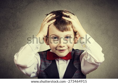 Confused little boy with hand on his had over grey background.