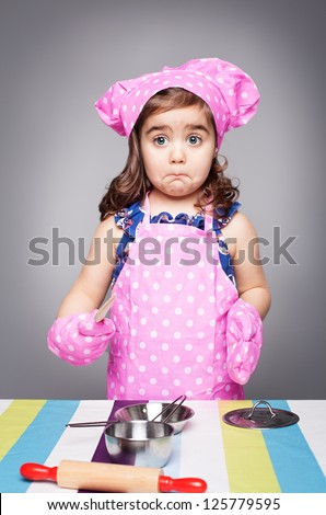 confused little cook in pink clothes holding a wooden spoon - stock photo