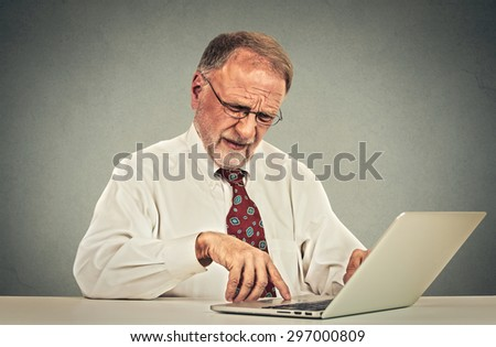Confused looking elderly mature man with glasses sitting at table working typing on laptop computer  - stock photo