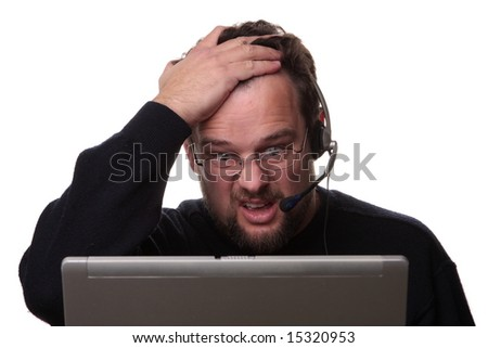 Confused looking 30-something computer operator on white background wearing phone headset