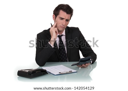 Confused man holding calculator - stock photo