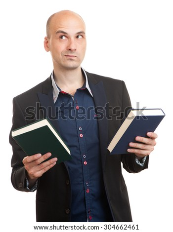 confused man holding two books in hands, deciding which one to choose. isolated - stock photo