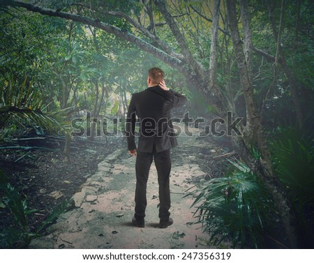 Confused man is lost in the forest - stock photo