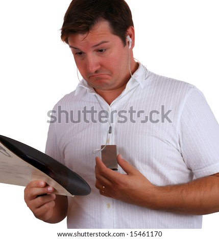 Confused man listening to his mp3 player and looking at the vinyl record - stock photo